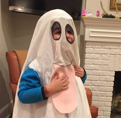 A little boy dressed up like a silly ghost.